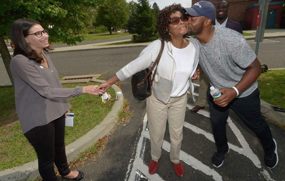 Candidate Eloisa Menendez and Kadeem Roberts' campaign worker Paul Stevens greet voter Carolyn Walker, center, at Kendall Elementary School as District A Democrats head to the polls Tuesday as part of a primary election for two seats on the Norwalk Common Council in November.
