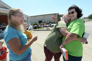 LCM school bus driver Carrie Richard hugs Jenni Anderson, the mom of several of her students as Anderson's mother Jennifer Miller looks on as they run into one another to get supplies at First Baptist Church in Mauriceville Tuesday. Businesses, churches and residents were all impacted by flooding from Tropical Storm Harvey, and are deep in the early stages of recovery from their losses. Photo taken Saturday, September 9, 2017 Kim Brent/The Enterprise