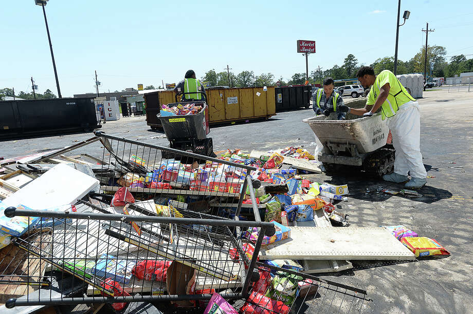 Workers unload another cart of trash to one of several dumpsters filling the parking lot at the Market Basket in Mauriceville Tuesday. Employees and contractors have been cleaning and dumping shelves full of products that have been or may have been spoiled by flooding. Assistant Manager Reagan Stanfield says once completed clearing the store and drying out the interior, the corporate office will decide if the store will be renovated or a new market opened on a parcel of land they own behind the current location on FM 62. Businesses, churches and residents were all impacted by flooding from Tropical Storm Harvey, and are deep in the early stages of recovery from their losses. Photo taken Saturday, September 9, 2017 Kim Brent/The Enterprise Photo: Kim Brent / BEN