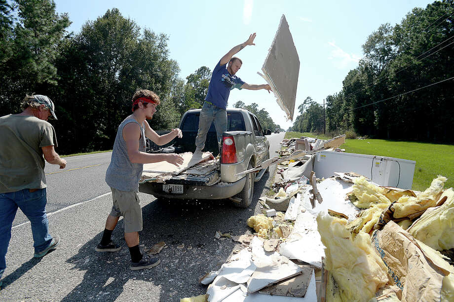 Dillion Schmidt (left) and Devin Lange toss debris from the back of their pick-up truck while they and D. Roy Harrington (far left) work cleaning flood damaged Serenity Oaks Ministries in Mauriceville Tuesday. The men all have flood damage to their own homes, but have been too busy working at other establishments and homes to address their own issues yet. Businesses, churches and residents were all impacted by flooding from Tropical Storm Harvey, and are deep in the early stages of recovery from their losses. Photo taken Saturday, September 9, 2017 Kim Brent/The Enterprise Photo: Kim Brent / BEN