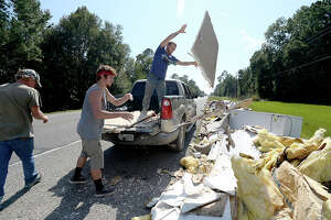 Dillion Schmidt (left) and Devin Lange toss debris from the back of their pick-up truck while they and D. Roy Harrington (far left) work cleaning flood damaged Serenity Oaks Ministries in Mauriceville Tuesday. The men all have flood damage to their own homes, but have been too busy working at other establishments and homes to address their own issues yet. Businesses, churches and residents were all impacted by flooding from Tropical Storm Harvey, and are deep in the early stages of recovery from their losses. Photo taken Saturday, September 9, 2017 Kim Brent/The Enterprise