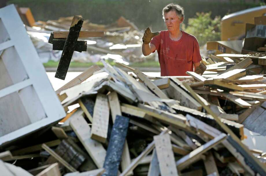 Jeff Lefkowitz piles debris in front of his flooded Meyerland home on Tuesday,   Photo: Melissa Phillip, Staff / © 2017 Houston Chronicle