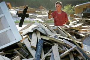 Jeff Lefkowitz piles debris in front of his flooded Meyerland home on Tuesday,