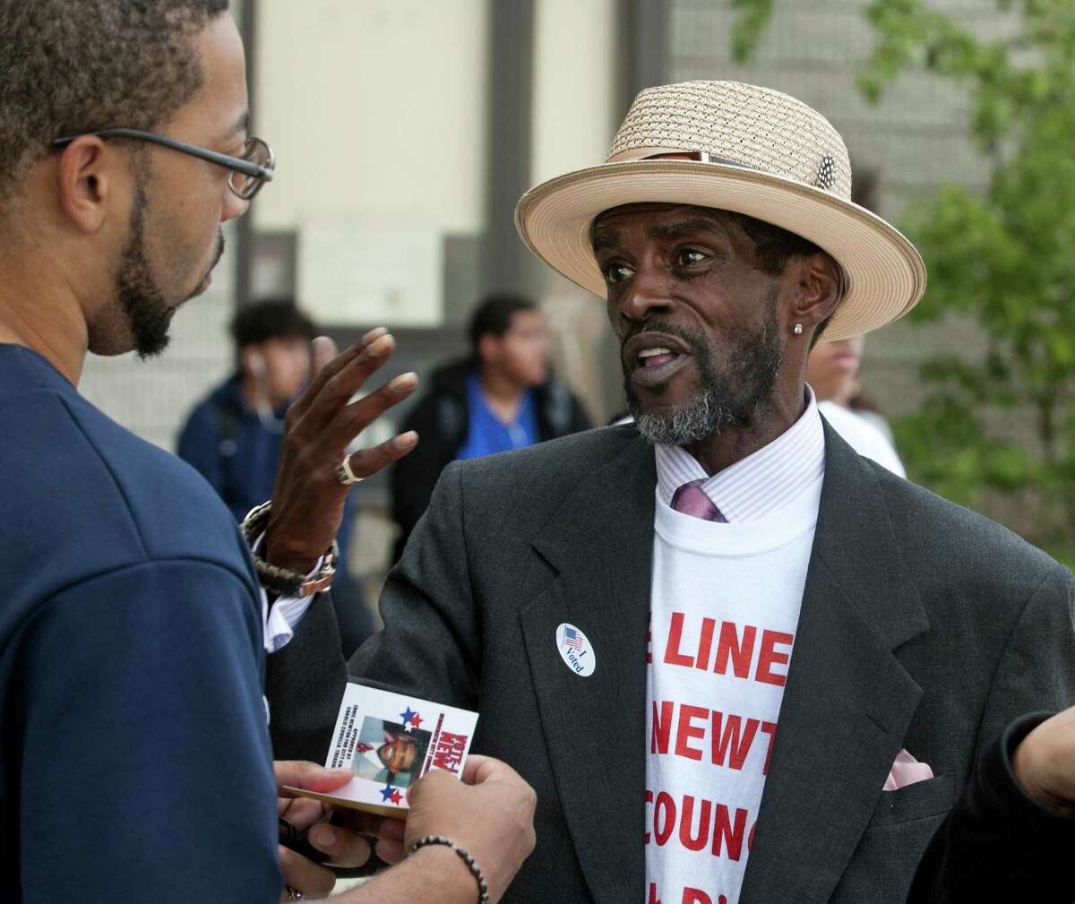 On Primary Day, Bridgeport City Council candidate Ernest Newton speaks to voter Walter Williams, left, in front of Dunbar School.