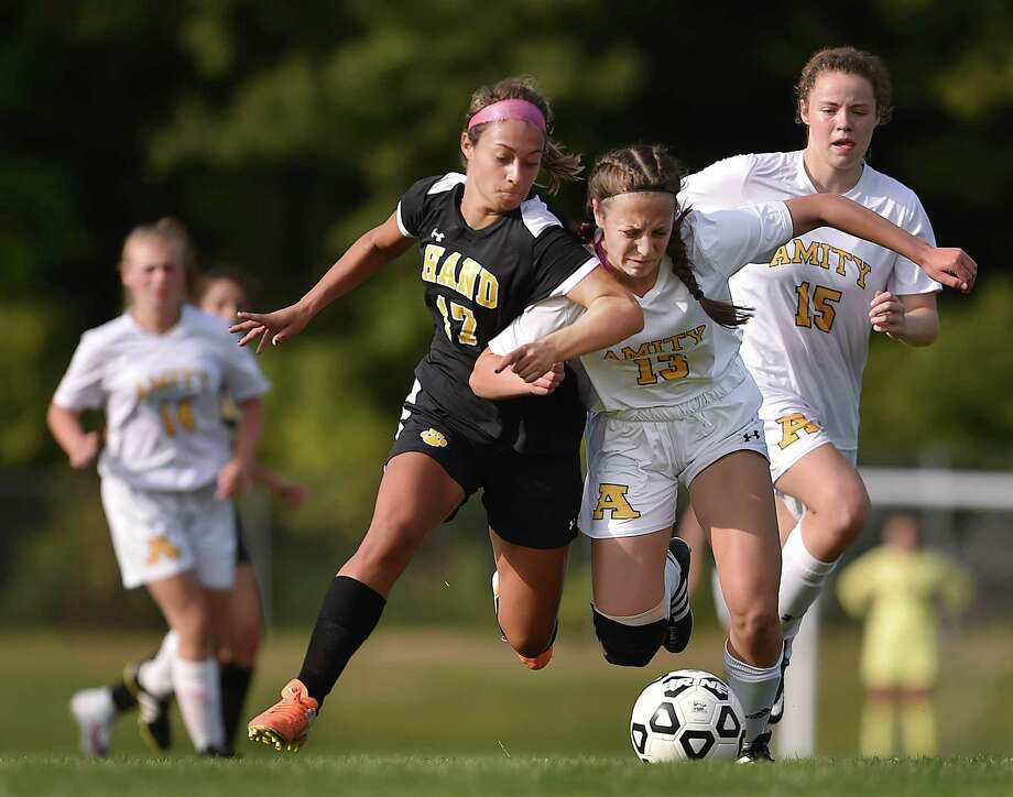 Hand senior forward Taylor Scully battles Amity's Erin Marin (#13) and Kaitlyn Price (#15), to maintain possession of the ball, Tuesday, September 12, 2017, at Amity High School in Woodbridge. Scully scored two goals for Hand, defeating the Spartans, 2-1. Photo: Catherine Avalone, Hearst Connecticut Media / New Haven Register