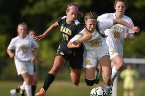 Hand senior forward Taylor Scully battles Amity's Erin Marin (#13) and Kaitlyn Price (#15), to maintain possession of the ball, Tuesday, September 12, 2017, at Amity High School in Woodbridge. Scully scored two goals for Hand, defeating the Spartans, 2-1.