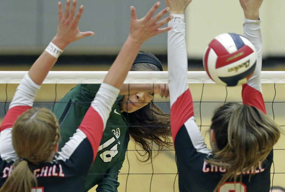 Reagan's Kyla Waiters (center) jams a shot through the Churchill defense at the net during a district volleyball match at Littleton Gym on Sept. 12, 2017. Photo: Tom Reel /San Antonio Express-News / 2017 SAN ANTONIO EXPRESS-NEWS