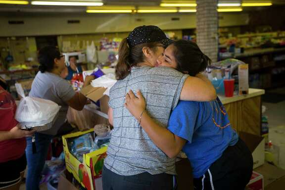 Angie Torres and Lia Hernandez, residents of the South Texas coastal town of Tivoli, console each other Tuesday at the town's makeshift donation and community center.