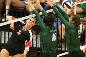 Churchill's Cate Buckingham (left) had a team-high 15 kills in a four-set loss to top-ranked Reagan. Photo by Tom Reel/Express-News