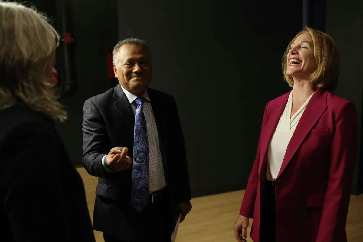 Mayoral candidate Jenny Durkan, right, laughs as debate moderator Enrique Cerna of KTCS9 flips a coin to determine who will answer questions first during the debate, Tuesday, Sept. 12, 2017 at Seattle University.