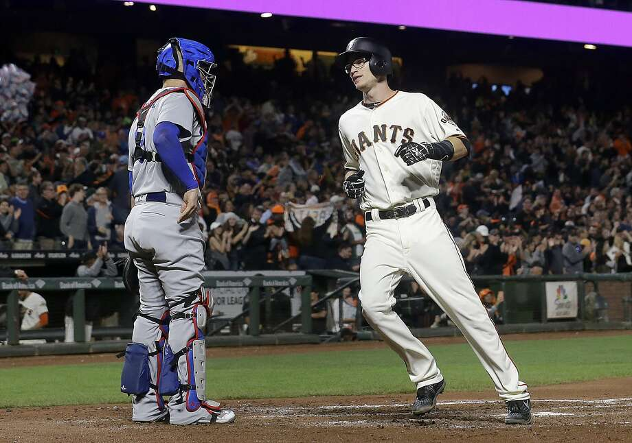 San Francisco Giants' Kelby Tomlinson, right, crosses the plate next to Los Angeles Dodgers catcher Yasmani Grandal after hitting a solo home run during the third inning of a baseball game in San Francisco, Tuesday, Sept. 12, 2017. (AP Photo/Jeff Chiu) Photo: Jeff Chiu, Associated Press
