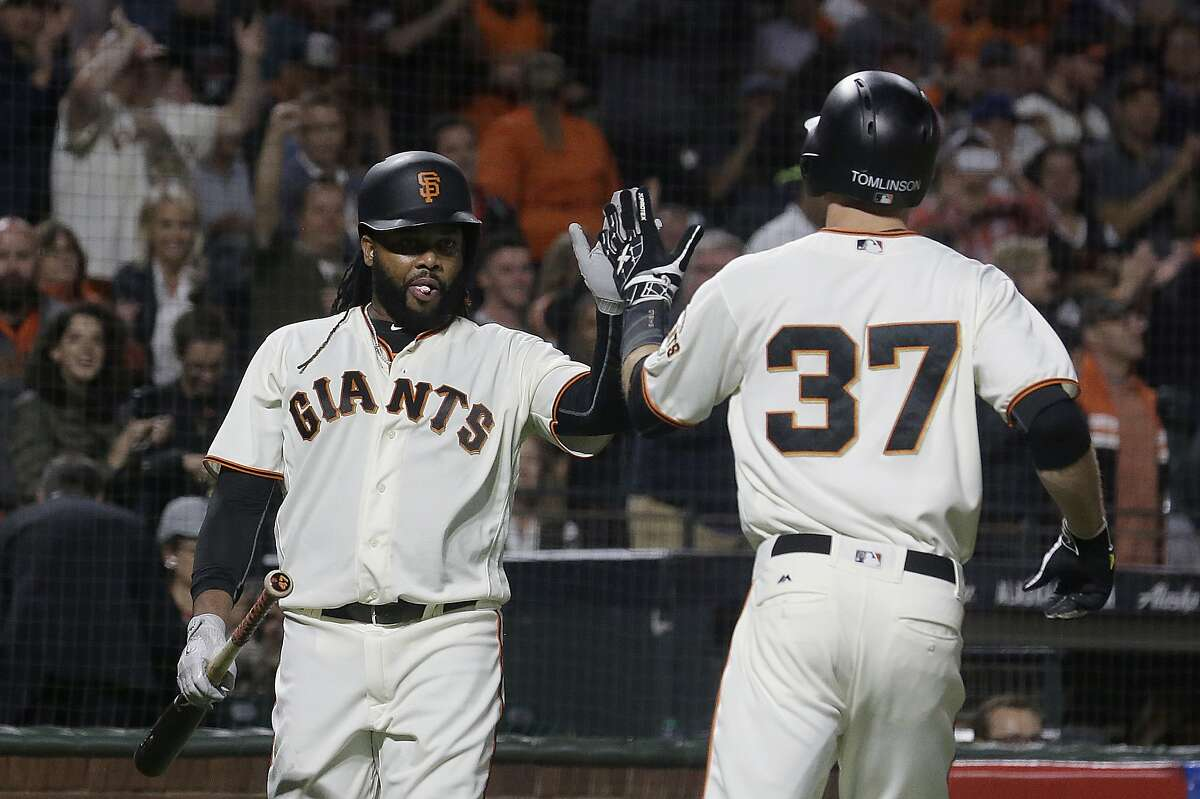 San Francisco Giants' Kelby Tomlinson, right, is congratulated by Johnny Cueto after hitting a solo home run against the Los Angeles Dodgers during the third inning of a baseball game in San Francisco, Tuesday, Sept. 12, 2017. (AP Photo/Jeff Chiu)