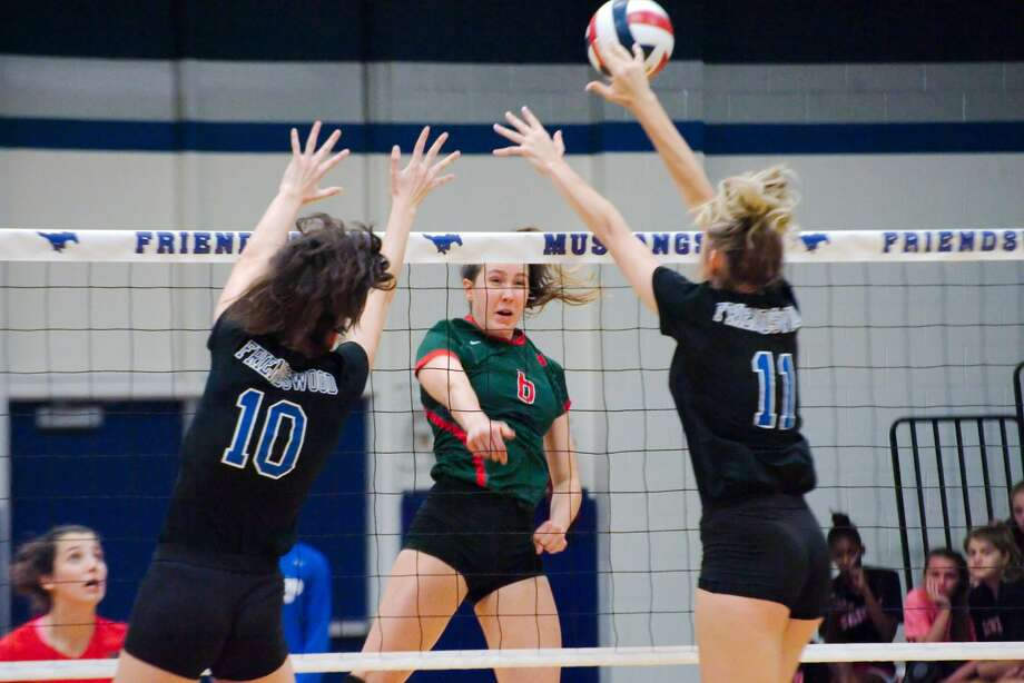 Friendswood's McKenna Fridye (10) and Friendswood's Faith Marabella (11) try to block a shot by Woodland's Courtney Heiser (6) Tuesday, Sep. 12.