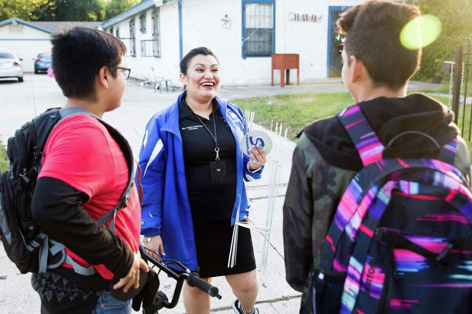 Dwight Middle School Principal Yvonne Hernandez talks with former students about voicing support for Dwight Middle School during Viva South San, a block walking event in support of South San Antonio ISD, near Dwight Middle School in San Antonio, Texas on December 12, 2016. Ray Whitehouse / for the San Antonio Express-News Photo: Ray Whitehouse, Photographer / For The San Antonio Express-News / B641358283Z.1