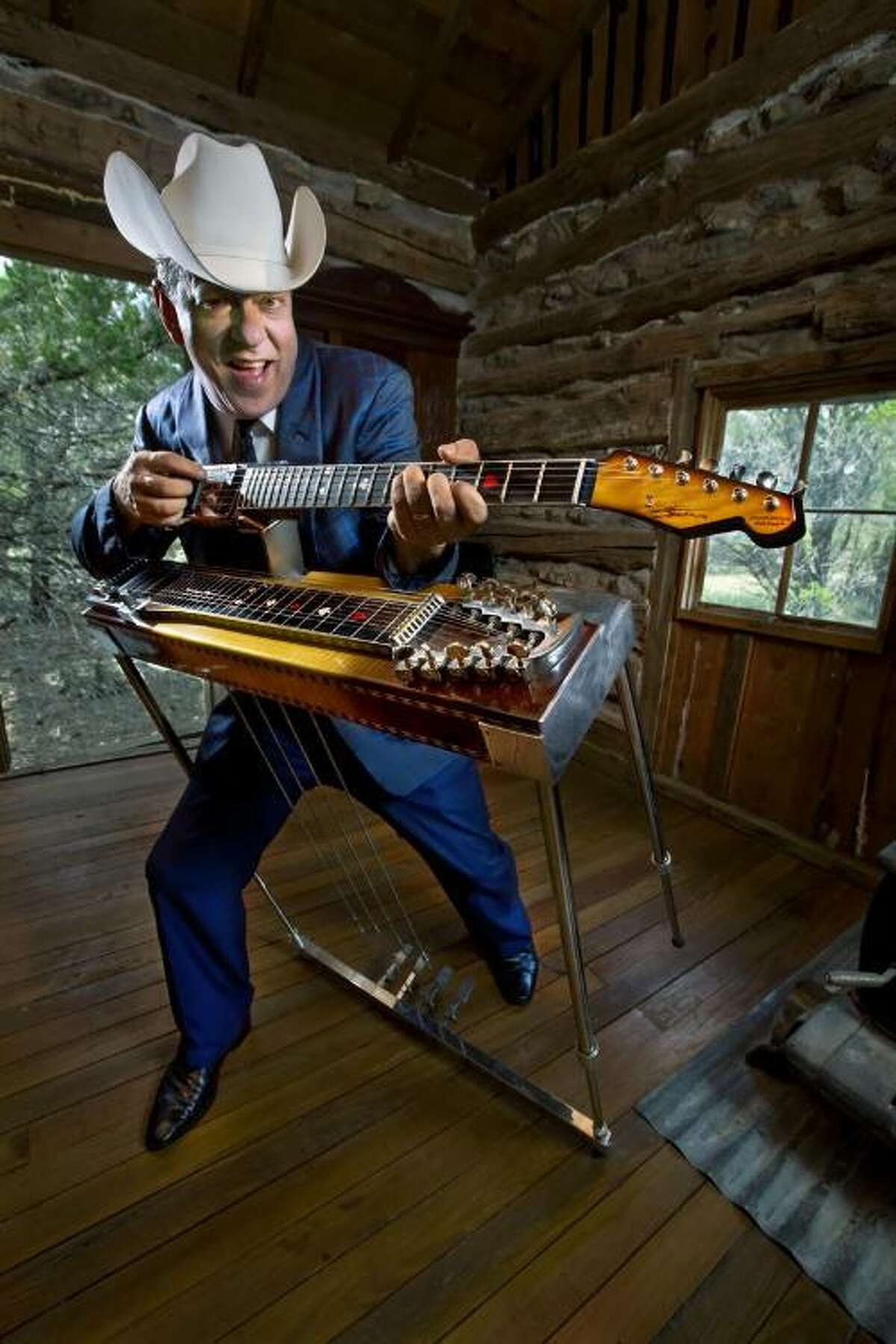 """Country music veteran and former Wilton resident Junior Brown shows off the latest iteration of his """"guit-steel,"""" a double-necked guitar hybrid that combines a traditional guitar with a full-sized lap steel guitar."""