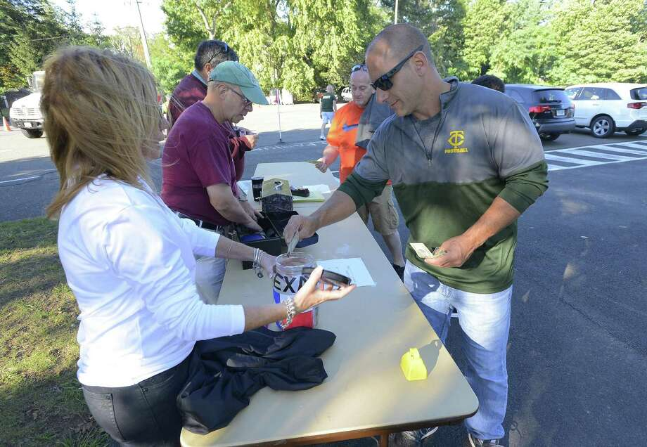 Keith Pensiero of Stamford makes a donation towards relief efforts in Texas being collected during the football game at Trinity Catholic High School on Friday, Sept. 8, 2017 in Stamford, Connecticut. The school has collected over $10,000 towards relief, that will be distributed through various agencies, such as the American Red Cross. Photo: Matthew Brown / Hearst Connecticut Media / Stamford Advocate