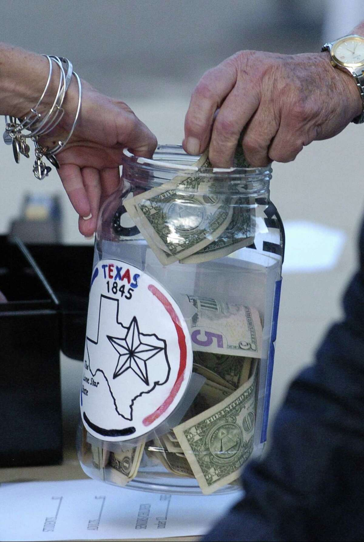 Attendees donate towards relief efforts in Texas, collected in a jar during the football game at Trinity Catholic High School on Friday, Sept. 8, 2017 in Stamford, Connecticut. The school has collected over $10,000 towards relief, that will be distributed through various agencies, such as the American Red Cross.
