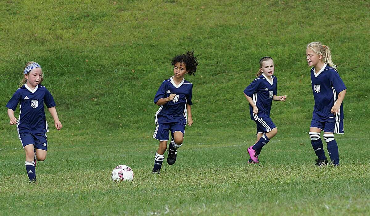 Wilton youth soccer players, from left, Grayson O'Donnell, Isabella Rios, Lauren Ely and Liesel Schmauch converge on a ball during their game last weekend.