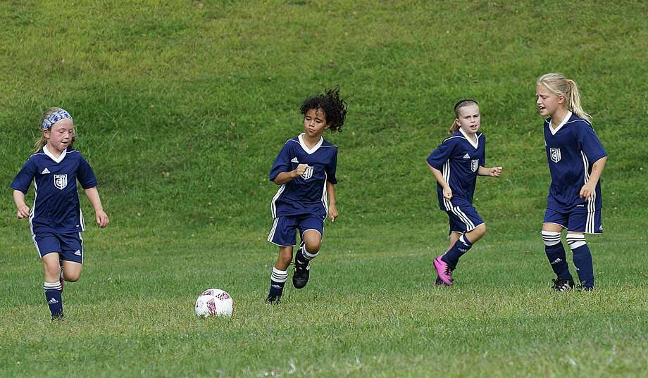 Wilton youth soccer players, from left, Grayson O'Donnell, Isabella Rios, Lauren Ely and Liesel Schmauch converge on a ball during their game last weekend. Photo: John Nash / Hearst Connecticut Media / Norwalk Hour