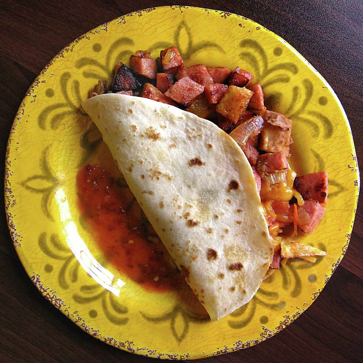 Taco Deluxe with country sausage, potatoes, beans, cheese and pico de gallo on a handmade flour tortilla from Natalie's Mexican Cafe.