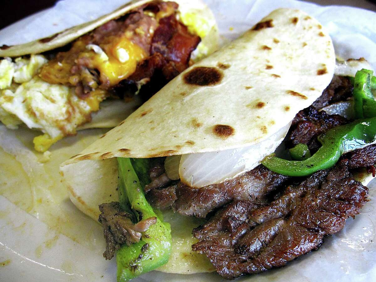 Beef fajita ranchera taco, foreground, and a Taco Tex-Mex with bacon, eggs, beans and cheese, both on handmade flour tortillas, from Natalie's Mexican Cafe.