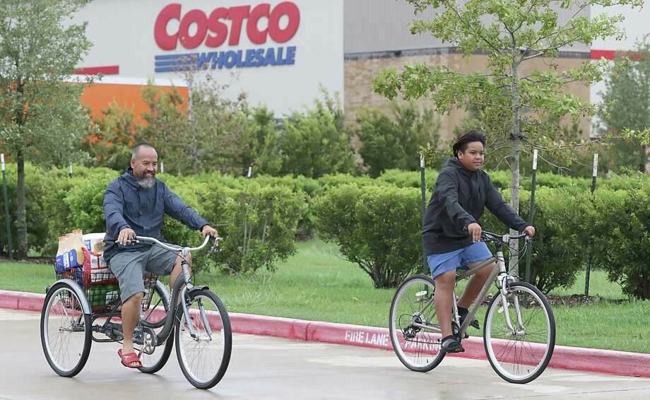 A man and his son pick up supplies on their bicycles from Costco in Pearland. Photo: THOMAS B. SHEA, AFP/Getty Images / AFP or licensors