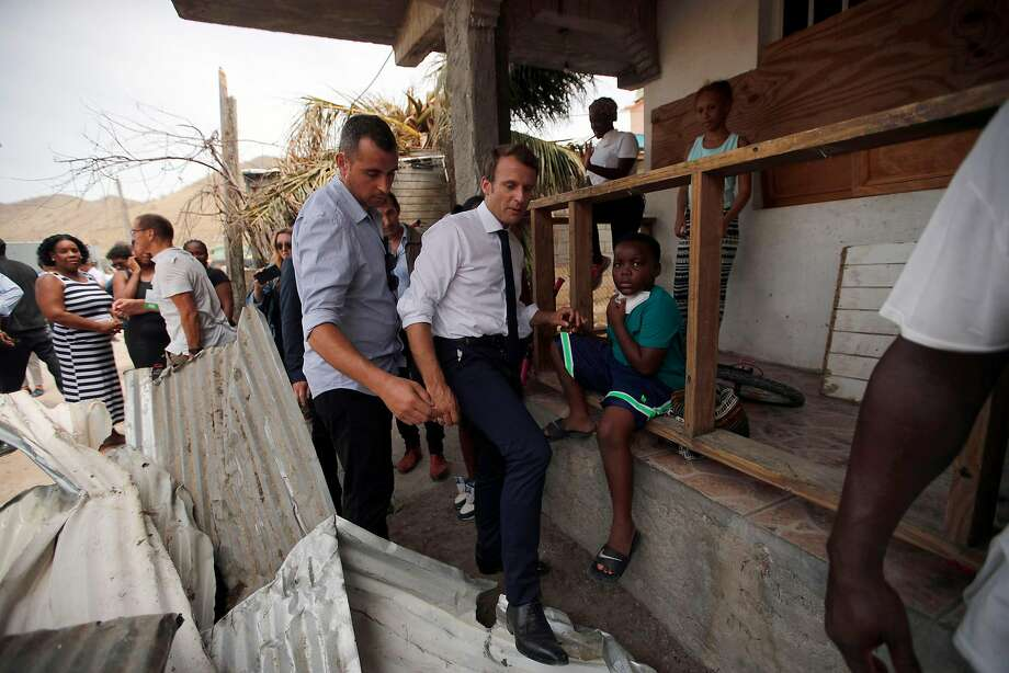 French President Emmanuel Macron (center) makes his way through debris on St. Martin island. Photo: CHRISTOPHE ENA, AFP/Getty Images