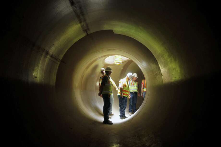 San Antonio Water System officials stand Friday afternoon June 15, 2012 inside a newly-installed 96 inch sewer pipe during a tour of the installation.. The 96 inch pipe runs for several miles at the end of a $103 million, 32-mile-long sewer line the San Antonio Water System is building to serve the South Side. Photo: William Luther, Staff / San Antonio Express-News / ¨ 2012 WILLIAM LUTHER