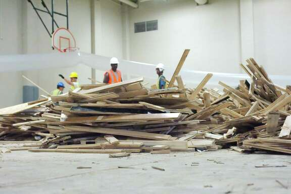 Contract workers remove wood flooring from the gym at Brookside Intermediate School in Friendswood as the school rebuilds.
