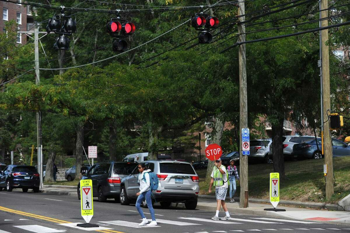 A Stamford High School student crosses Strawberry Hill Avenue under the watch of crossing guard Jack Maloney in Stamford, Conn. on Wednesday, Sept. 13, 2017. A traffic light was recently installed in front of Stamford High, along with two crossing guards, to make crossing the busy street safer.