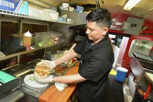 Chef Gino España makes a grilled pork Torta for a customer during lunch hour at Tacos El Azteca Don Juan food truck along Main St. on Wednesday September 13, 2017 in Norwalk Conn.