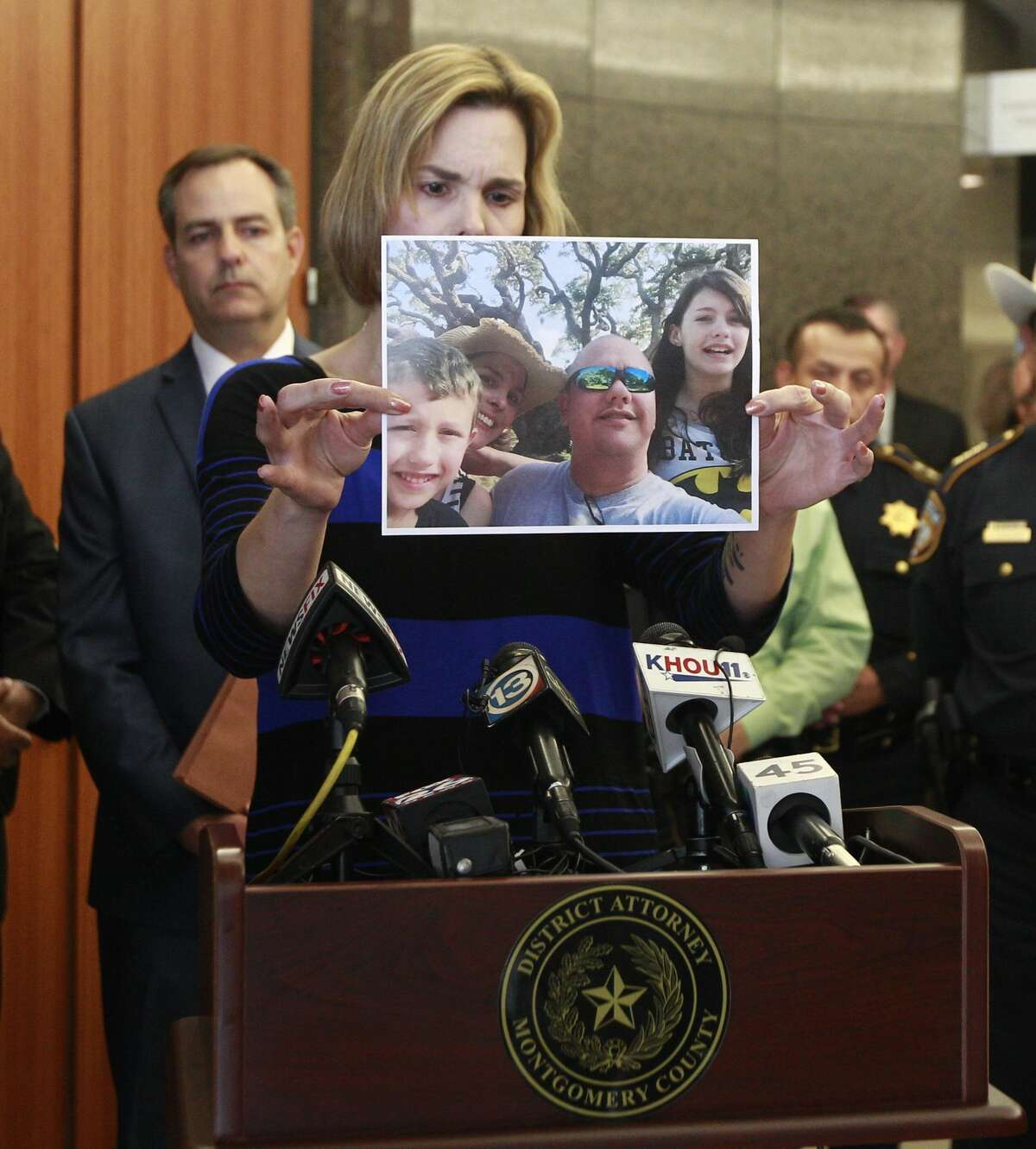 Kathleen Goforth, widow of Harris County Sheriff's Deputy Darren Goforth, shows photos of her family during a press conference at the Harris County Civil Courthouse, Wednesday, Sept. 13, 2017, in Houston. Shannon Miles, 32, pleaded guilty to capital murder and was sentenced to life without parole for fatally shooting her husband on Aug. 28, 2015, as he was filling up his patrol car at a gas station in Northeast Harris County.