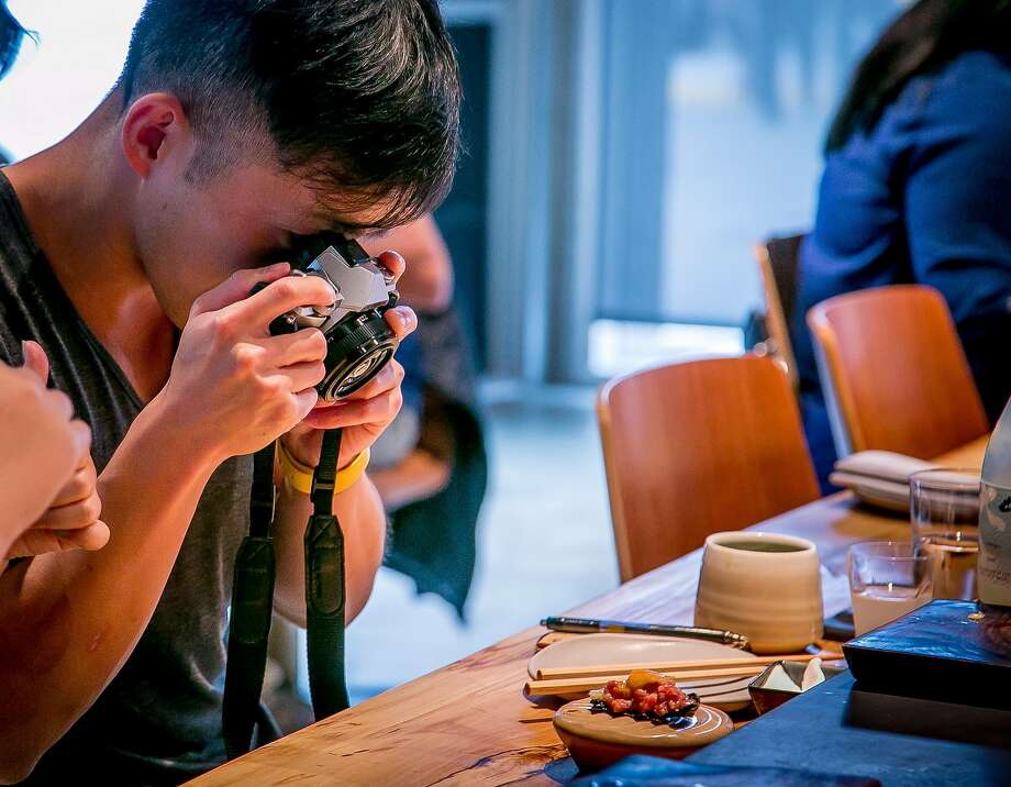 Ye Lu takes a picture of his food at Robin in San Francisco, Calif., on September 9th, 2017. Photo: John Storey, Special To The Chronicle