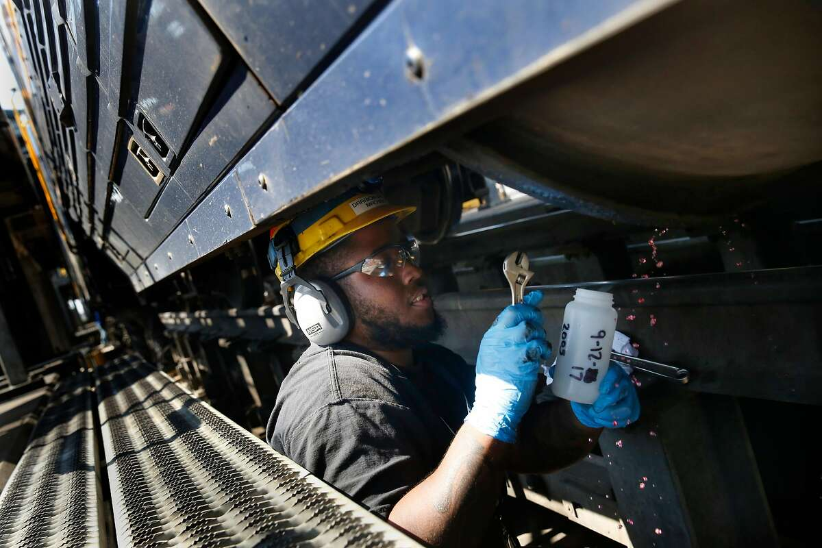 Darrion Brown, Amtrak machinist, takes a sample of renewable diesel from the fuel tank on a Capital Corridor locomotive for testing for contaminants, degredation and to make sure it meets quality standards at the Amtrak Maintenance Facility on Tuesday, September 12, 2017 in Oakland, Calif.