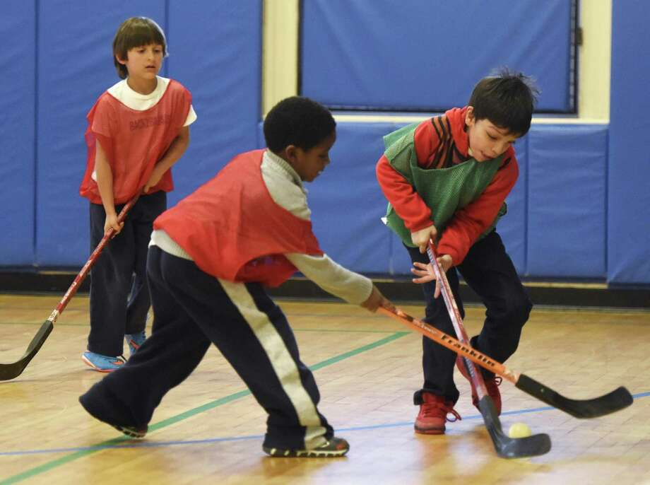 Grant Wall, center, 6, and Kayden Jimenez, right, 7, battle for the puck as Antonio Mitkov, left, 6, watches during a game of floor hockey — one of several after-school activities available at the Boys & Girls Club in Greenwich. Balancing after-school activities is part of being a family in Greenwich. Photo: Tyler Sizemore / Hearst Connecticut Media / Greenwich Time