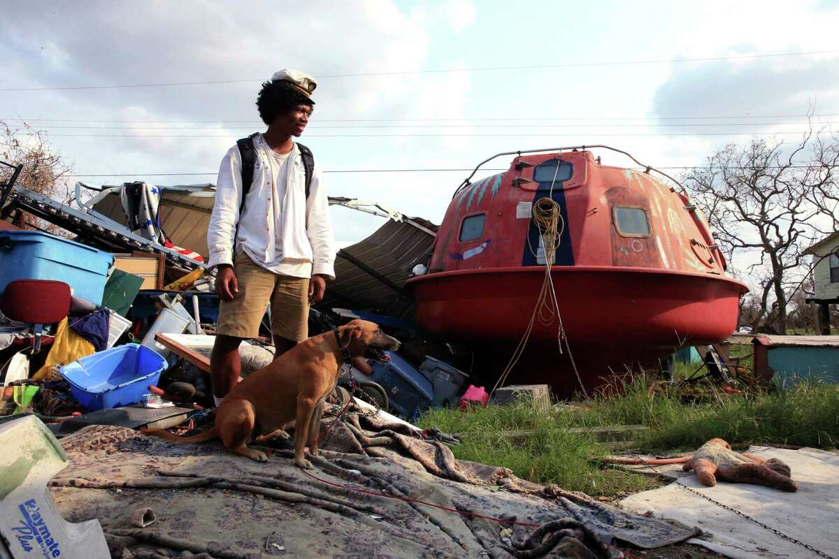 """In a Sept. 6, 2017 photo, Davonn Phothiboupha stands near a """"hurricane pod"""" that he stayed in, bought by Linda Caster, a resident of Holiday Beach in Aransas County, Texas, as Hurricane Harvey made landfall. Three people and two dogs stayed inside the pod when Hurricane Harvey made its second landfall with 130 mph winds in Aransas County on Aug. 26. and Phothiboupha said it saved their lives."""