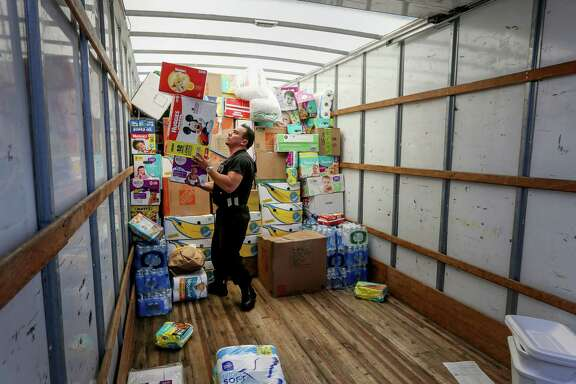 "Antonio Rodriguez, a police officer from Hyde Park, New York, balances several boxes of diapers while unloading a truck of donated supplies, Thursday, Sept. 7, 2017, in Houston. Rodriguez and a fellow officer drove 39 hours from New York, using their vacation days, to drop off the donated items. ""We just hope you guys would come up to New York if it happened to us,"" he said. ( Jon Shapley  / Houston Chronicle )"
