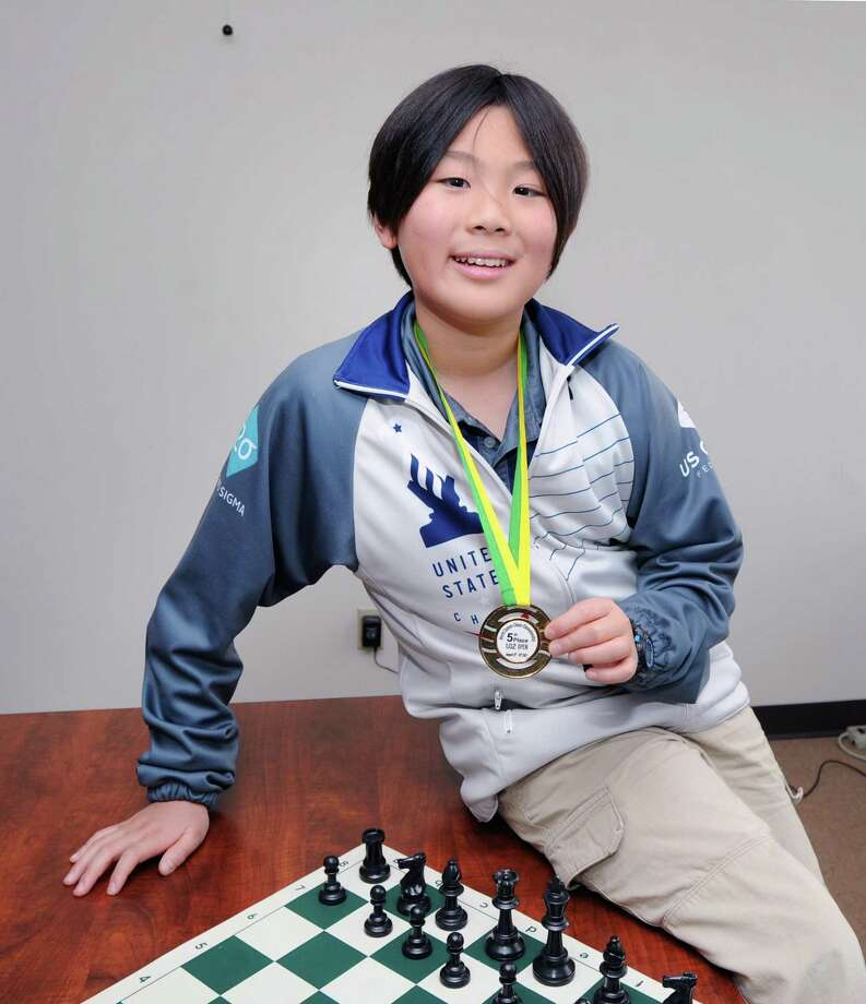 Max Lu, 11, of Greenwich, holds the medal he won during the recent World Cadets Chess Championship in Brazil as he poses at the Greenwich Time, Conn., Tuesday, Sept. 12, 2017. Lu placed 5th in his age division at the championship. Photo: Bob Luckey Jr. / Hearst Connecticut Media / Greenwich Time