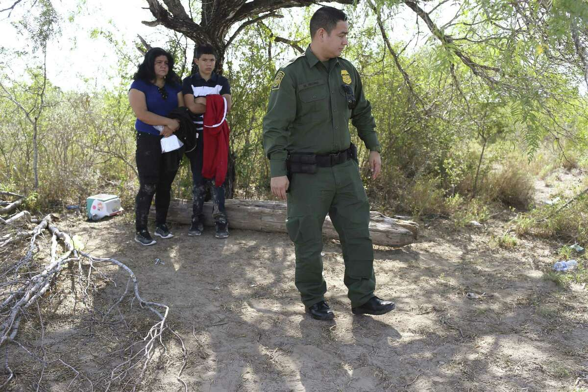 A Border Patrol agent stands near detained Central American families crossing into the U.S. in western Starr County, Tuesday, Sept. 12, 2017.