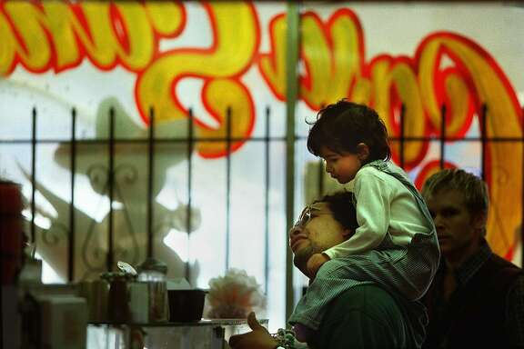 BURRITO2/12APR99/MN/BW--Rupert Moncada and his daughter Emily stood in line for burritos at Casa Sanchez on 24th Street Monday.  Moncada has considered getting a tattoo, but has not done it yet. By Brant Ward/Chronicle