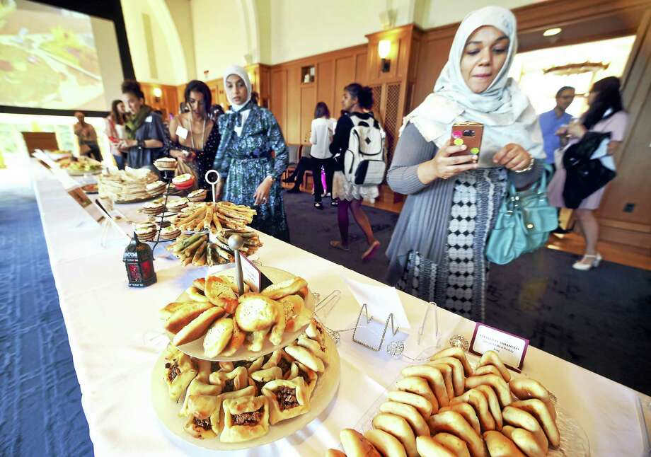 Salma Fagir, right, originally from Sudan, documents the food at a reception launching the Sanctuary Kitchen program hosted by CitySeed at the Greenberg Conference Center in New Haven  recently. Photo: Arnold Gold / Hearst Connecticut Media / New Haven Register