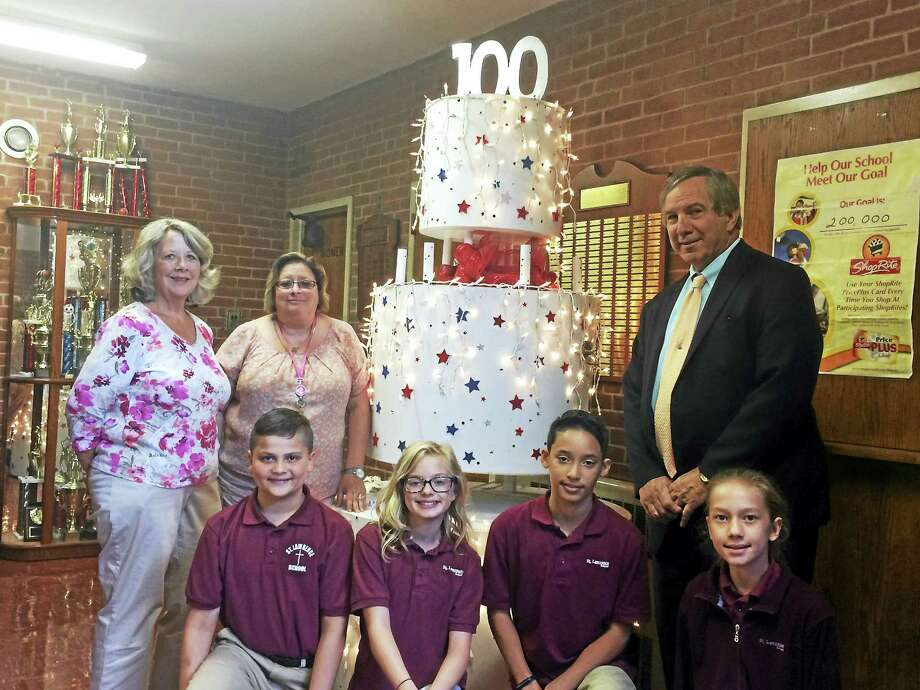 Saint Lawrence School Principal Paul DeFonzo, standing at right, 100th Anniversary Celebration Chairwoman Mary Jane Morrissey, far left, and librarian and marketing director Olympia Connolly pose with students Lee Senberg, Brooke Flaherty, Avery Lamothe and Josephina Lakaj in front of the schools ornamental 100th Anniversary cake. Photo: Mark Zaretsky / Hearst Connecticut Media