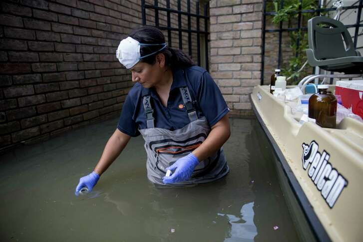 A worker collects water samples in neighborhoods affected by flooding from Hurricane Harvey in Houston, Sept. 5, 2017. Hurricane Harvey cut a path through industrial corridors, raising concerns about pollution and runoff, and GriffinÕs property lies a few hundred yards from a Superfund site that was inundated in the storm. (Eric Thayer/The New York Times)
