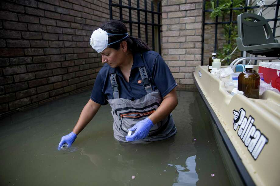 A worker collects water samples in neighborhoods affected by flooding from Hurricane Harvey in Houston, Sept. 5, 2017. Hurricane Harvey cut a path through industrial corridors, raising concerns about pollution and runoff, and GriffinÕs property lies a few hundred yards from a Superfund site that was inundated in the storm. (Eric Thayer/The New York Times) Photo: ERIC THAYER, STR / NYT / NYTNS