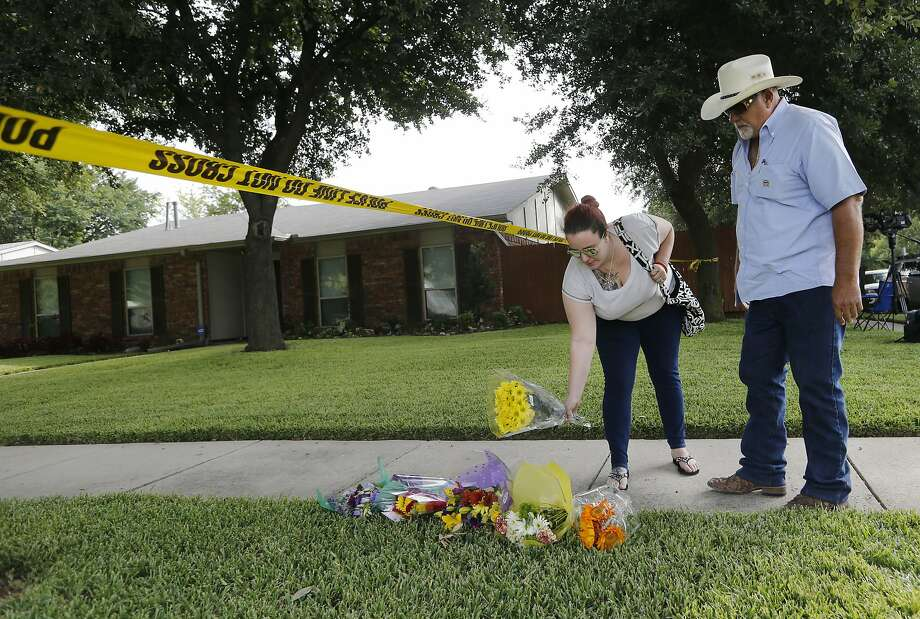 FILE - Kelsey Moss places flowers at a makeshift memorial site with her father Hal Moss of Plano, Texas, before saying a prayer for the eight victims in a shooting on West Spring Creek Parkway in Plano on Tuesday, Sept. 12, 2017. Wednesday, as part of a settlement, The Local Public House will cancel its liquor license. Parents of three of the victims accused the bar of negligence for serving Spencer Hight, the gunman responsible. Photo: Vernon Bryant, Associated Press