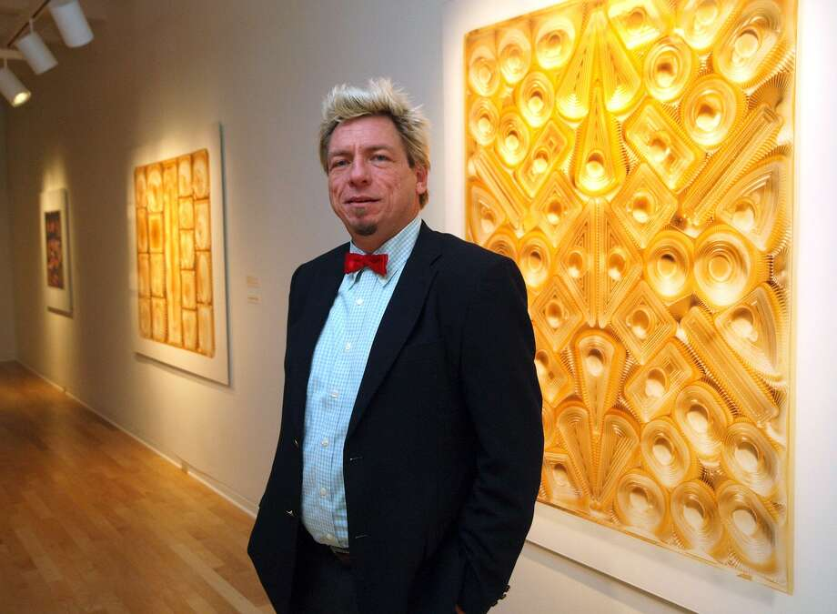 """Chuck Ramirez posed with his work in """"Chocolate: A Photography Exhibition"""" at the San Antonio Museum of Art in 2008. Almost seven years after his death in 2010, Ramirez is the subject of a career survey at the McNay Art Museum. Photo: Express-News File Photo / SPECIAL TO THE EXPRESS-NEWS"""