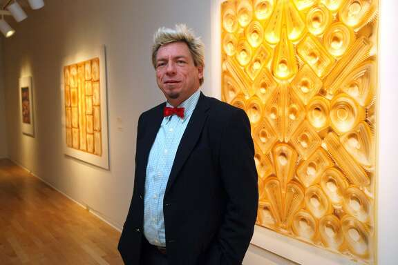 """Chuck Ramirez posed with his work in """"Chocolate: A Photography Exhibition"""" at the San Antonio Museum of Art in 2008. Almost seven years after his death in 2010, Ramirez is the subject of a career survey at the McNay Art Museum."""