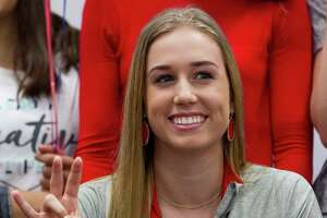 Willis setter Abby Irvine makes the University of Houston hand sign after signing to play volleyball with the Cougars during a signing ceremony at Willis High School Friday, Nov. 11, 2016, in Willis.