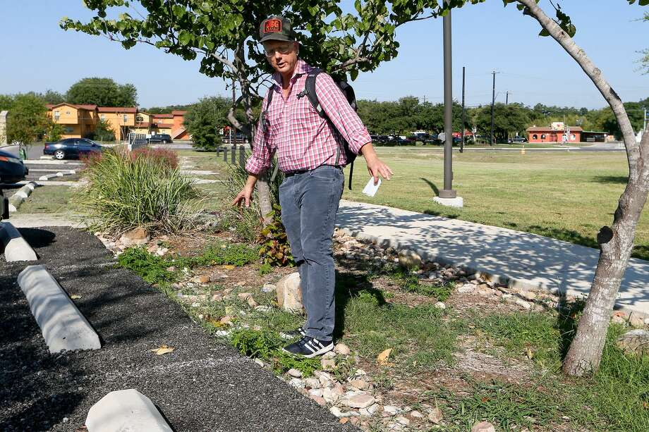 Brian Zabcik with Environment Texas talks about rain gardens and bioswales, while standing in a bioswale bordering the parking lot at Mission Branch Library, 3134 Roosevelt Avenue, during a tour of several green infrastructure features there on Sept. 12, 2017. Bioswales are designed to manage runoff from hard surfaces, such as parking lots, and consist of engineered soils and plants. Photo: Marvin Pfeiffer /For The San Antonio Express-News / Express-News 2017