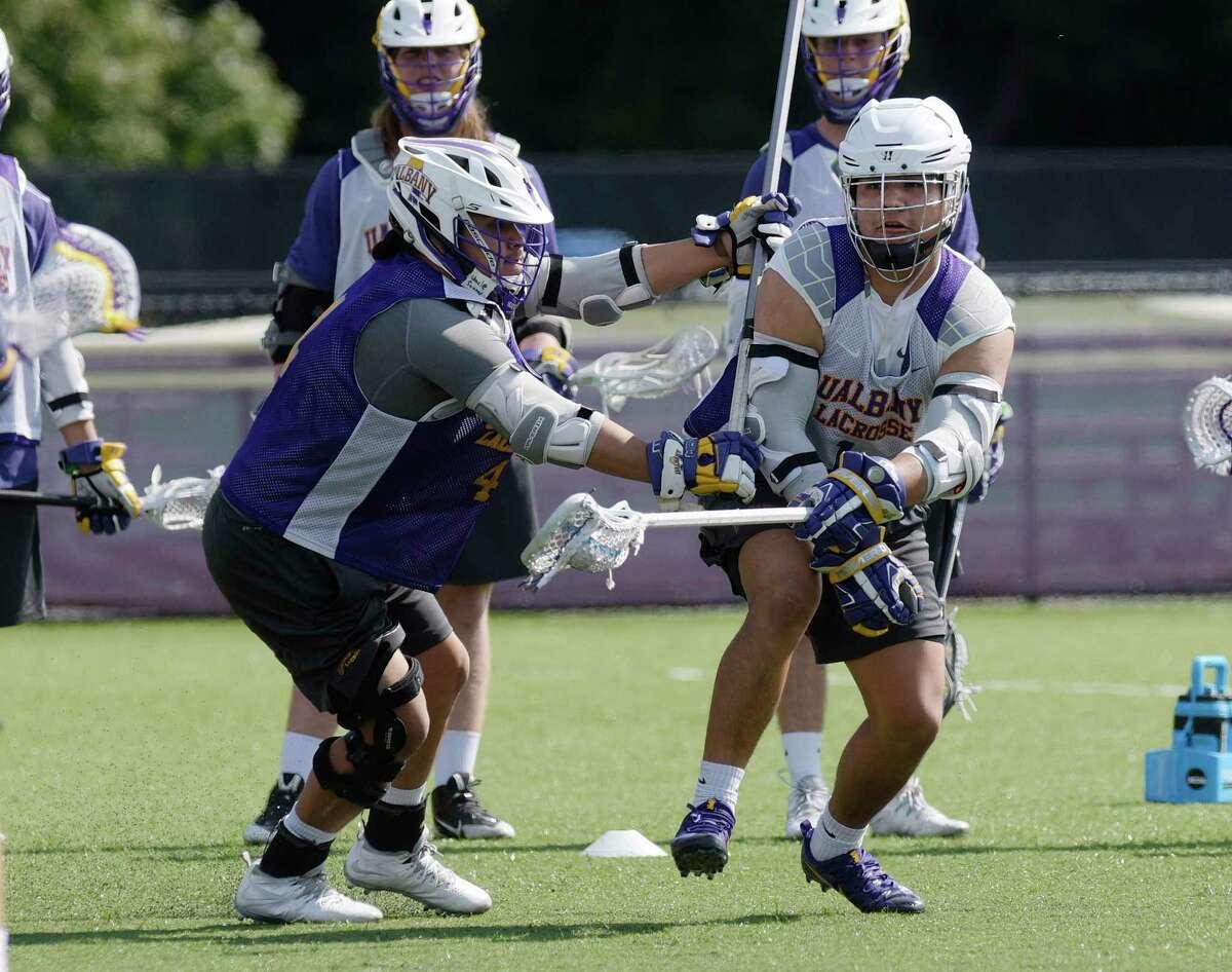 University at Albany men's lacrosse player, Tehoka Nanticoke, right, runs through drills during practice on Wednesday, Sept. 13, 2017, in Albany, N.Y. (Paul Buckowski / Times Union)